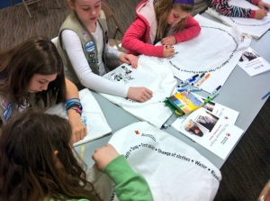 A Girl Scout troop colors preparedness kits during a Red Cross Pillowcase Project session.