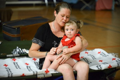 """June 26, 2016. Charleston, West Virginia. Floods. Mother Tianna Butler and her daughter Skyler. Randall and his wife Tianna Butler recently moved into an upstairs apartment with their two-year-old daughter named Skyler. Tianna is 8 months pregnant. """"Last Thursday the rains started. It came up really fast. When we saw the hillside crumble from the water we called 911, who told us it was safer to stay in the top part of the house rather than risk moving outdoors with all the flooding going on"""", says Randall. """"I was getting contractions from all the stress,"""" says Tianna. She and Skyler were rescued on Saturday at 12:30 a.m. and brought to the Red Cross shelter at Capital High School in Charleston. Randall joined them later. """"We really appreciate what the Red Cross has done,"""" says Randall. """"I never had any encounter with the Red Cross nor do I know anyone who has dealt with them, but everything they did has been top-notch; they are really professional."""" But the Butlers remain concerned about the future. The money that they put into moving and fixing up their new apartment is now gone with the floodwaters. Having so recently moved, they hadn't yet purchased any home insurance. """"I hope we get some assistance or we will be on the sidewalk somewhere,"""" says Randall. Photo by Daniel Cima for the American Red Cross"""