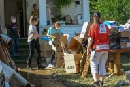 """June 26, 2016. Clendenin, West Virginia. Floods. Kari Thompson, a member of the """"Fire Breather Fitness"""" a CrossFit group from Charleston, join other members of the fitness group who are volunteering to help clean the flooded home in Clendenin of an aunt of one of their members. The home was flooded when the nearby Elk River broke its banks on Thursday following heavy rains. In the background are the children (Evelyn, Tura and Ethan - left to right) of an another member of the fitness group who are helping out as well. Photo by Daniel Cima for the American Red Cross"""