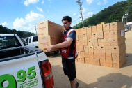 June 26, 2016. Clendenin, West Virginia. Floods. In an area of Clendenin which was completely submerged during the floods site, American Red Cross volunteer and State Senator, Chris Walters, helps distribute cleanup kits. Photo by Daniel Cima for the American Red Cross