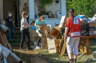 "June 26, 2016. Clendenin, West Virginia. Floods. Kari Thompson, a member of the ""Fire Breather Fitness"" a CrossFit group from Charleston, join other members of the fitness group who are volunteering to help clean the flooded home in Clendenin of an aunt of one of their members. The home was flooded when the nearby Elk River broke its banks on Thursday following heavy rains. In the background are the children (Evelyn, Tura and Ethan - left to right) of an another member of the fitness group who are helping out as well. Photo by Daniel Cima for the American Red Cross"