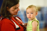 June 29, 2016. Charleston, West Virginia. Red Cross employee Mary Williams with one-year-old Sarah Shafer who, along with his mother and grandparents, is a flood victim from Clendenin, West Virginia. She and her family are staying at Capital High School gymnasium in Charleston, which has been turned into a Red Cross shelter. Photo by Daniel Cima for the American Red Cross