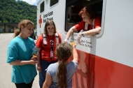 June 29, 2016. Clay, West Virginia. Red Cross volunteer Marie Loyons serves food to Loretta King and her eight-year-old daughter Byany King with Red Cross employee Mary Williams in the background. The Red Cross Emergency Response Vehicle is at Clay High School at a community relief distribution point to assist flood victims from Clay, West Virginia. The vehicle contains 300 hot meals of chicken dumplings and mixed vegetables, along with pudding or a cookie for desert. Photo by Daniel Cima for the American Red Cross