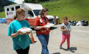 June 29, 2016. Clay, West Virginia. Red Cross employee Mary Williams helps flood victims Loretta King and her eight-year-old daughter Byany King carry their food to their vehicle. They were served a hot meals by an Red Cross Emergency Response Vehicle at Clay High School at a community relief distribution point to assist flood victims from Clay, West Virginia. The vehicle contains 300 hot meals of chicken dumplings and mixed vegetables, along with pudding or a cookie for desert. Photo by Daniel Cima for the American Red Cross