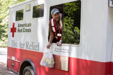 June 30, 2016. Birch River, West Virginia. American Red Cross worker Bernard Stuart holds a bag of snacks and water for a resident in Birch River, West Virginia. The emergency response vehicle traveled through neighborhoods, delivering nearly 150 hot meals to the community. Photo by Marko Kokic for the American Red Cross