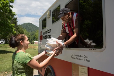 June 30, 2016. Birch River, West Virginia. American Red Cross worker Bernard Stuart hands Ashley Harlow a container of pulled pork in Birch River, West Virginia. The emergency response vehicle traveled through neighborhoods, delivering nearly 150 hot meals to the community. Photo by Marko Kokic for the American Red Cross