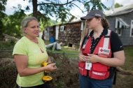 "June 30, 2016. Richwood, West Virginia. Robin Cowell and American Red Cross worker, Mary Williams, survey the damage to her Richwood, West Virginia, home. ""When I lay in bed at night I think that all these people care. They came. All these volunteers came,"" said Cowell. Photo by Marko Kokic for the American Red Cross"