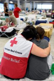 August 16, 2016. Gonzales, Louisiana. Red Cross relief worker Elizabeth Stander takes time to visit with people affected by recording flooding, including Courtney Robinson, at the Red Cross shelter in Gonzales, Louisiana. Photo by: Marko Kokic/American Red Cross