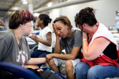 August 16, 2016. Gonzales, Louisiana. Courtney Robinson (center) says she is nearly certain that her home is destroyed because of the record flooding in southern Louisiana. She is staying at a Red Cross shelter with her children and husband. They fled with some essential items, such as food, water, and a change of clothes for them and their five children. Courtney shared their story with Red Cross relief worker Elizabeth Stander, and Rachel Ambeau, who is also displaced and staying at the Red Cross shelter, in Gonzales, Louisiana. Photo by: Marko Kokic/American Red Cross