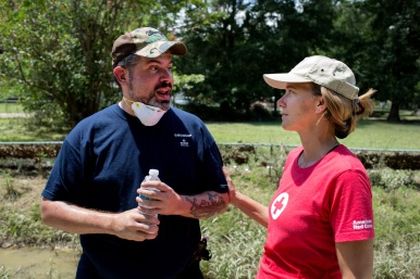 "August 18, 2016. Denham Springs, Louisiana. ""I can't cry in front of my family,"" says Navy veteran Benjamin Bonin, who tells the harrowing story of floodwaters rushing through his neighborhood in Denham Springs to Red Cross relief worker Lynette Nyman. ""I heard screams from across the street,"" says Bonin. He evacuated with his family as soon as he could, but not before helping others who were more vulnerable and unable to get out alone. ""I pulled people out all day and all night."" Bonin welcomed iced water from the Red Cross during flood relief efforts. Photo by: Marko Kokic/American Red Cross"