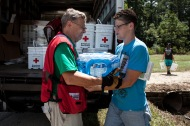 August 19, 2016. Denham Springs, Louisiana. Del Ruiseco gives Red Cross relief supplies, including clean-up kits and water, to Melanie Taylor. Photo by: Marko Kokic/American Red Cross