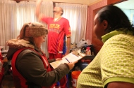 Disaster Program Specialist Emily Probst shares fire safety information with Cleveland resident Teressa Jackson, as Zeus McClurkin installs a smoke alarm