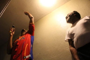Zeus McClurkin installs a smoke alarm in the home of Cleveland resident Mikael Raheem