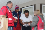 Cleveland resident Mikael Raheem receives fire safety information from Disaster Program Specialist Emily Probst, as CEO Mike Parks and Zeus McClurkin observe