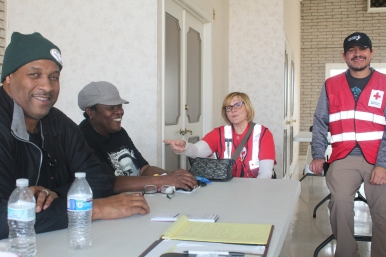Residents Ricky and Patricia Tunstall receive assistance from Red Cross volunteer disaster workers Rita Szy7mczak and Eric Reyes