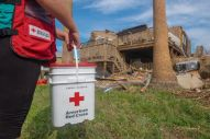 September 2, 2017. Port Aransas, Texas. Red Cross volunteer carries a cleanup kit to a home in Port Aransas, Texas. Photo by Chuck Haupt/American Red Cross