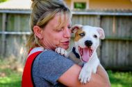 "September 7, 2017. Sugar Land, Texas. Red Cross Volunteer Julie Fox from the Western and Central New York Region gets to visit the 10-week-old Labrador-Pitt Bull mix puppy that she is going to adopt at the home of a local animal rescuer. Julie, on her first deployment, was at a kitchen in Sugar Land, Texas, when a Hurricane Harvey victim, who was leaving the state, dropped the puppy off to her and quickly left. Julie lost her home to a fire last year, which her dog and cat died. ""Everything happens for a reason,"" she said, ""this puppy was meant for me to take back home."" She appropriately named her new pet, Harvey. Photo by Chuck Haupt for the American Red Cross"