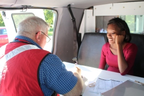 Red Cross volunteer Mark Cline assists E. 103rd St. resident Cara Hunt in the Disaster Van