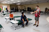 July 28, 2020. Edcouch, Texas Marc Lazerow of the American Red Cross welcomes the Cantu family to their cots at a Red Cross shelter for people displaced by Hurricane Hanna in Edcouch, TX on Tuesday July 28, 2020. Family units are grouped closer together while other cots are spaced further apart for social distance from others. Photo by Scott Dalton/American Red Cross
