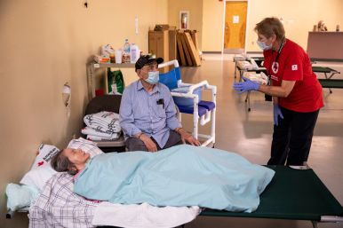 July 28, 2020. Edcouch, Texas Diana Buckley of the American Red Cross checks on Jose and his wife Maria Elvia, who needs hospice care, at a Red Cross emergency shelter for people displaced by Hurricane Hanna in Edcouch, TX on Tuesday July 28, 2020. Photo by Scott Dalton/American Red Cross